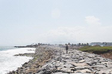 person walks along the rocks at Cape Coast