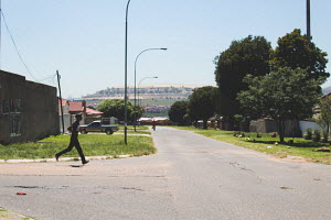 one man walks, while another man runs down the streets of Soweto