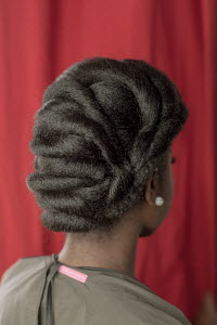 A lady gets her unrelaxed hair styled for a bridal show