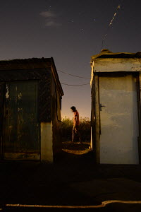 African man, alleyway, corrugated iron housing,
