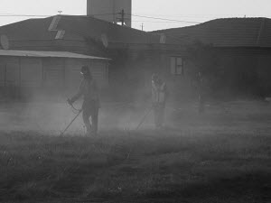 People cutting grass to clear the footpaths in Tsakane