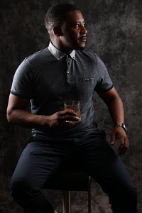 African male sipping whiskey.