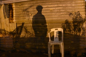 Phola Park, Ext 5, South of Johannesburg, Corrugated iron housing, Sundown, white plastic chair, shadows