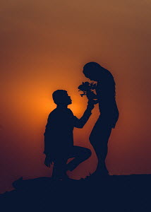 A man on bended knee passing a woman flowers with the sunset as their backdrop
