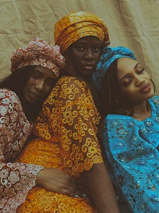 Three women in bright colors and traditional West African dresses